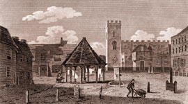 The market place in Enfield, Middlesex, in 1805, showing laundry being hung out to dry, a milestone, water pump, stocks and the imposing St Andrew's Church