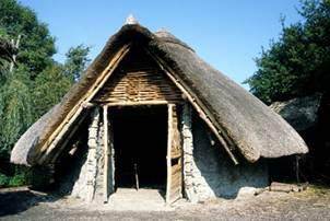 Reconstruction of a small Iron Age hut with a thatched roof
