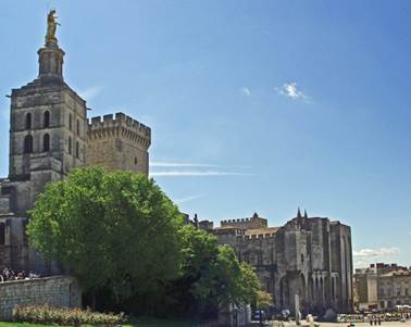 Avignon's imposing cathedral (dating from 12th century) and the old papal palace (enlarged from the original bishop's palace) are on the left, visible above the trees. The later palace (centre right) was built by Pope Clement VI. On the far right, modern buildings are tiny by comparison