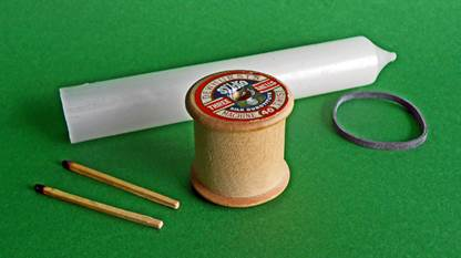 wooden cotton reel, an elastic [or rubber] band, a piece of wax candle and a couple of matchsticks